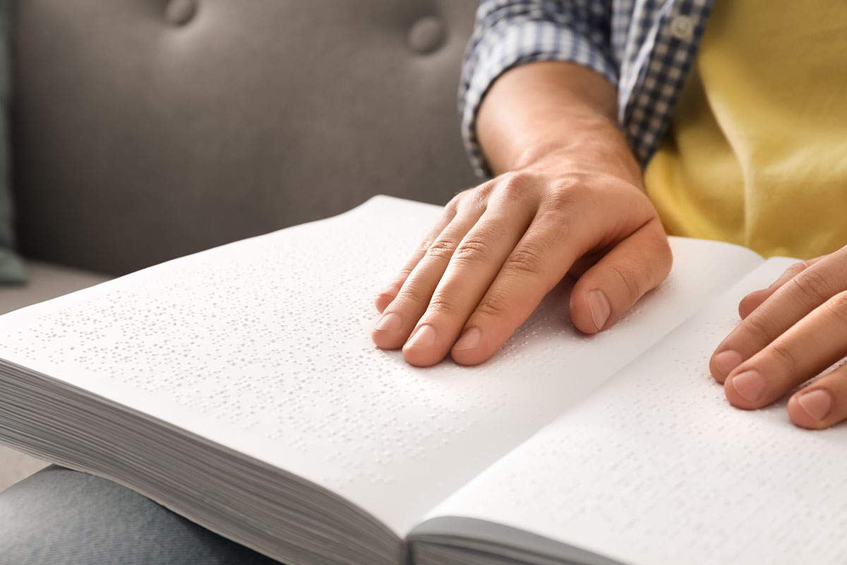 Close up image of a blind man reading a book written in Braille, seated on a sofa