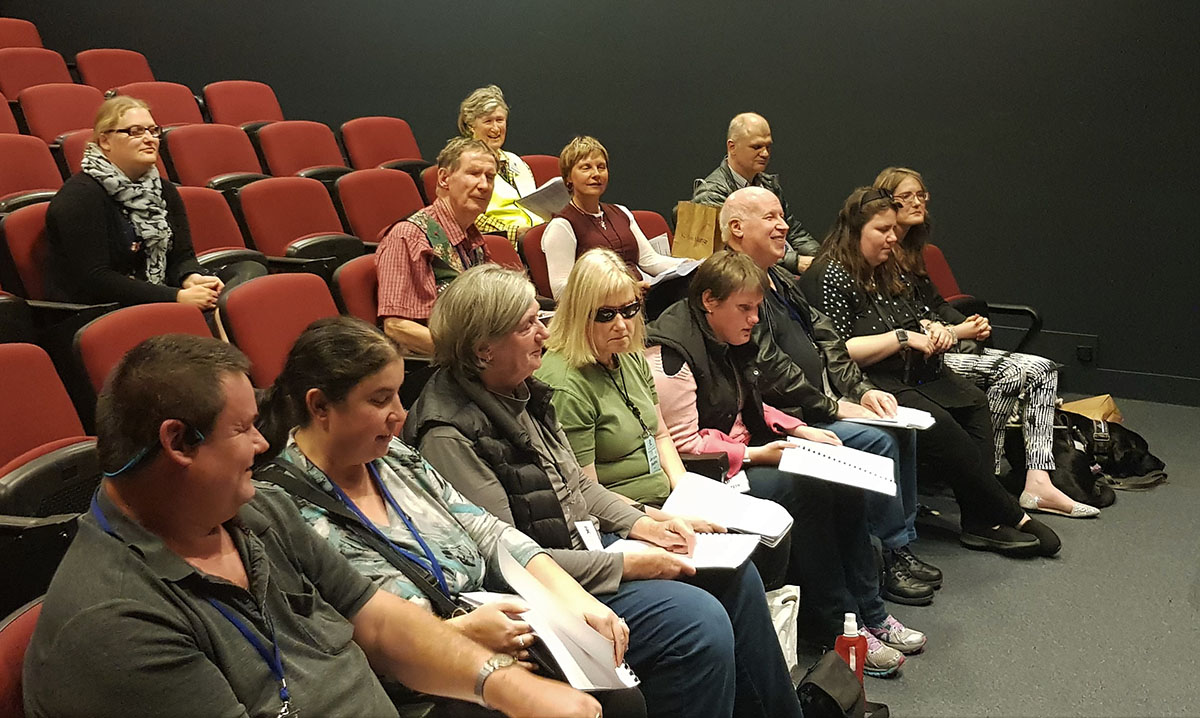 Group of people seated in an auditorium practicing a choir song