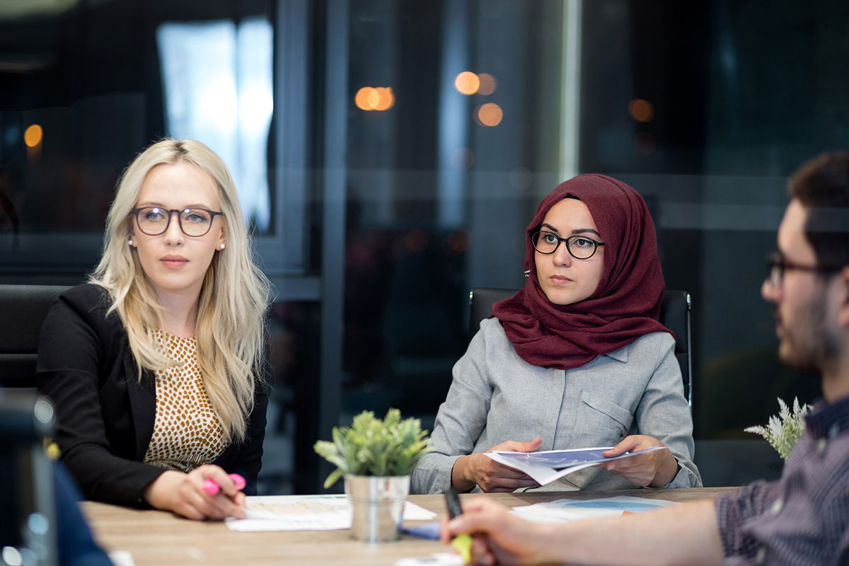 Three People Concentrating in a Meeting
