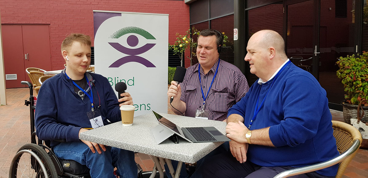 Three people participate in a radio interview at an outdoor table, a BCA banner is visible